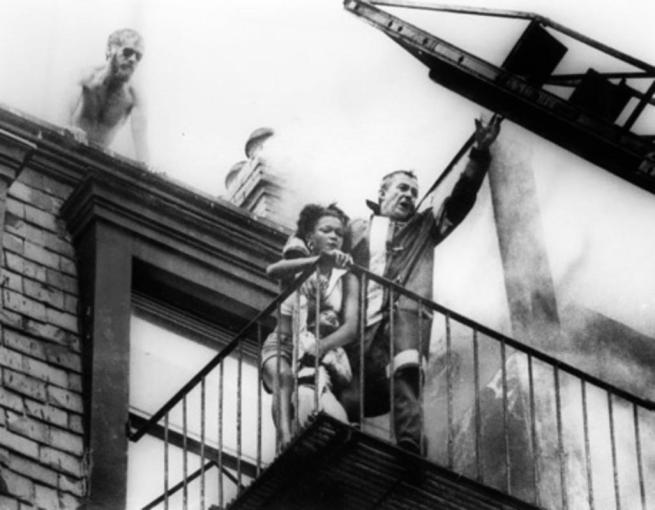 Boston firefighter Robert O'Neill is seen with Diana Bryant and Tiara Jones, age 2 years, and helicopter pilot Joe Green, above, prior to the fire escape collapse that would kill Bryant, at 129 Marlborough St. on July 22, 1975. Photo Stanley Forman